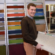 Geschäftsführer Hermann Schulte vor einer vielfältigen Auswahl an Teppichen